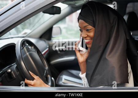 Elegante mujer vistiendo musulmán africano en negro el hijab sentada en automóvil, hablar por el teléfono móvil. Hermosa, joven chica sujetando con la mano en el volante, sonriendo.