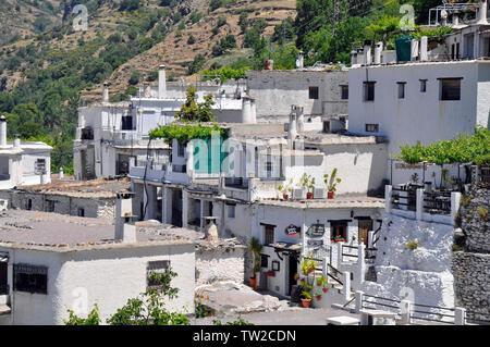 Las casas construidas en la ladera de la colina en la pintoresca aldea de montaña Pampaneira en las Alpujarras, Granada, España