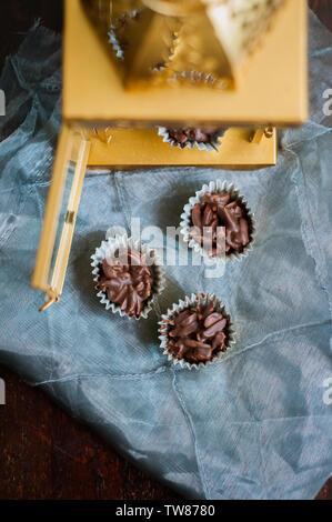 Almendras cubiertas con chocolate en tazas de papel dorado con faro de oro en el fondo.