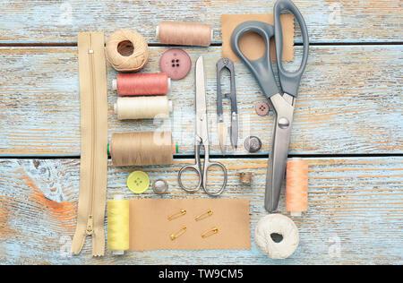 Hilos de colores y accesorios de costura sobre fondo de madera