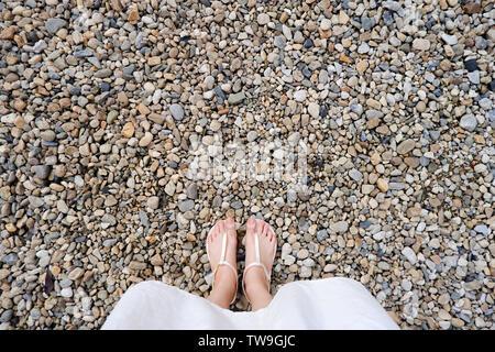 Selfie Joven de pies en zapatos de moda piedras en el suelo. Hermosa chica es permanente y delgado pie piernas visto desde arriba en la carretera Street. Zapato plano Foto de stock