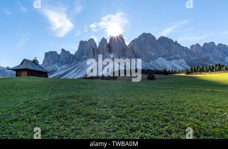 Sunburst sobre el Odle picos y capilla en Glatschalm, Puez Odle, dolomitas, Funes, provincia de Bolzano, Tirol del Sur, Italia