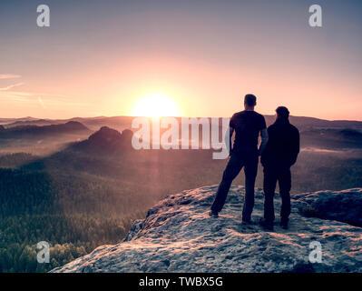 Los niños a los turistas permanecer juntos cerca uno del otro en la cumbre. Fogy paisaje de ensueño azul brumoso amanecer en un hermoso valle abajo