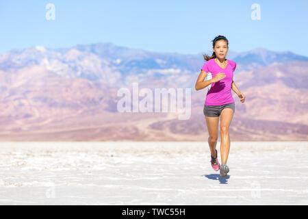 Ejecuta el deporte mujer atleta esprinta en trail run en el desierto. Fitness femenino runner en capacitación entrenamiento de sprint en pantalones cortos y camisetas. Colocar muscular deporte chica modelo fuera bajo un cielo azul.