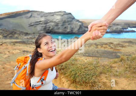 Mano - caminante mujer obtener ayuda sobre caminata sonriendo feliz superar el obstáculo. Turistas mochileros caminando sobre arena verde Papakolea Beach, en Big Island, Hawaii, USA. Pareja joven de viajar.