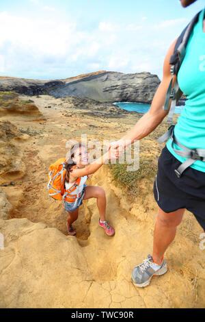 Ayuda - caminante mujer obtener mano de Senderismo Senderismo sonriendo feliz. Turistas mochileros caminando sobre arena verde Papakolea Beach, en Big Island, Hawaii, USA. Pareja joven viajar con mochilas.