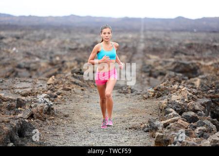 Runner mujer triatleta trail running cross country funcionando fuera del volcán. Atleta Femenina entrenamiento de jogging para carrera de maratón fuera en un bello paisaje en Big Island, Hawaii, USA.