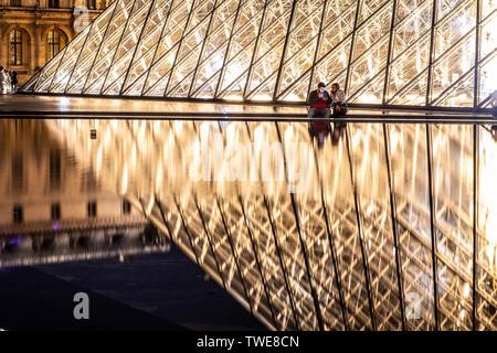 París, Francia, 04 de octubre de 2018: El Palacio del Louvre y la pirámide (por la noche) como entrada dentro del Museo del Louvre, los turistas paseos, tomar fotos