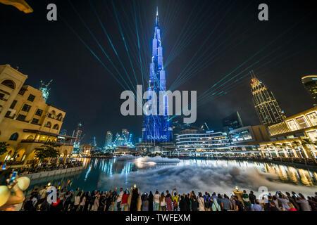 Las multitudes tienen teléfonos para capturar el impresionante espectáculo de luces del Burj Khalifa en Dubai. Foto de stock