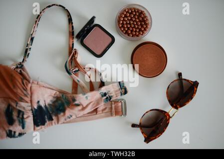 Bikini, sunglases y algunos productos de maquillaje en una tabla blanca