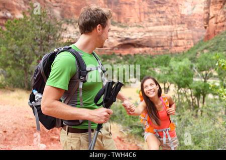 Mano - senderismo mujer obtener ayuda sobre caminata sonriendo feliz. Un estilo de vida activo excursionista pareja que viajaba. Hermosa raza mixta sonriente caucásico Asiático Femenino en el Parque Nacional de Zion, Utah, EE.UU..