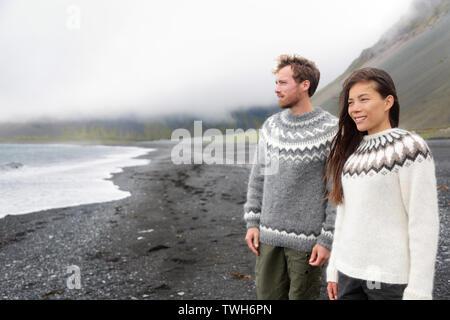 Islandia par vistiendo suéteres islandesa sobre la playa de arena negra. La mujer y el hombre en el típico modelo suéter islandés mirando al océano disfrutando de la vista de la naturaleza paisaje de mar océano. Foto de stock