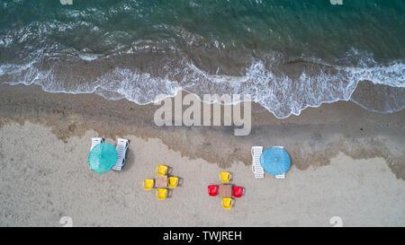Vista superior de la antena en la playa. Paraguas, la arena y el océano.