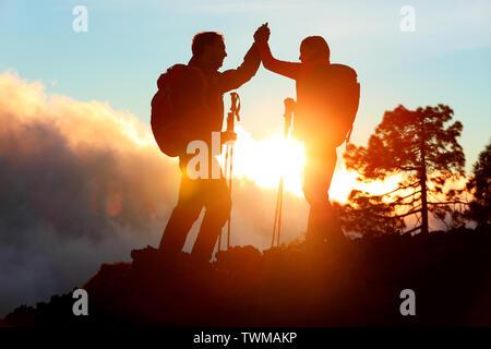 Senderismo de personas que llegan a la cumbre da alta superior a cinco en la cima de la montaña al atardecer. Excursionista feliz pareja silueta. Éxito, logros y realización de personas