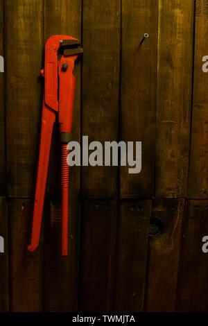 Old Orange llave de tubo colgado en la pared de madera