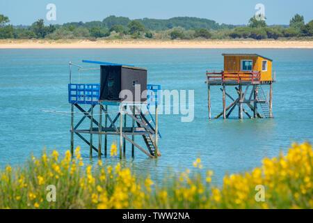 Típicas y coloridas cabañas de pesca de madera sobre pilotes en el Océano Atlántico cerca de La Rochelle, Francia