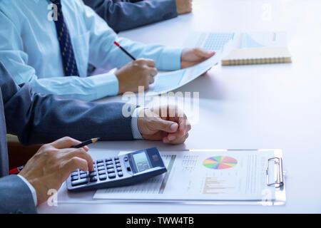 Empresarios en una sala de reuniones están revisando profundamente los estados e informes financieros para un retorno de la inversión o el análisis de riesgo de inversión.