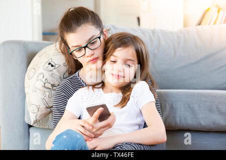 Dos hermanas sentado en frente del sofá mirando el smartphone