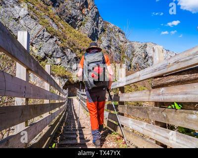 España, Asturias, Cordillera Cantábrica, senior hombre sobre una excursión cruzando un puente