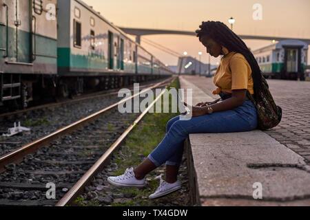 Mujer joven sentada en el andén en la estación de tren utilizando el portátil
