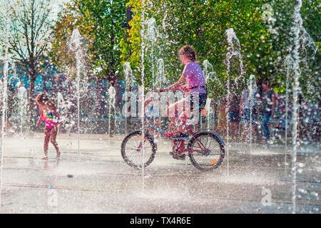 En verano, el calor, una niña de montar bicicleta entre fuentes, gente cool en chorros de agua Foto de stock