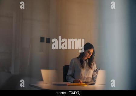 Joven Empresaria de trabajar hasta tarde en un escritorio en la oficina
