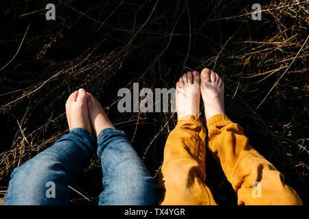 Los pies de la niña y su hermano mayor en la naturaleza, close-up