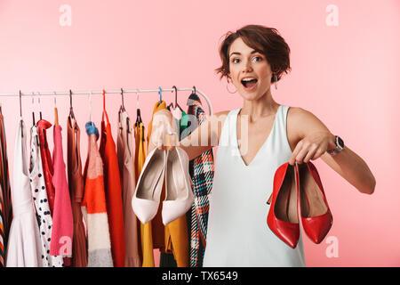 Sorprendido feliz hermosa mujer estilista desgastando posando con zapatos de vestir mientras stening cerca del montón de ropa sobre fondo de color rosa
