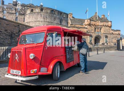 Rojo brillante vintage Citroën H van convierte a una salida de comida y bebida, con un cliente que se sirve, estacionado afuera del Castillo de Edimburgo, Escocia, Reino Unido.
