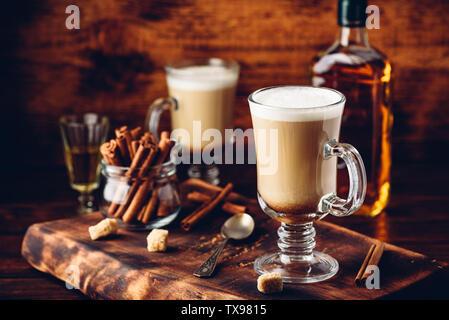 El café con el whisky irlandés y crema batida en cristal sobre superficie de madera rústica