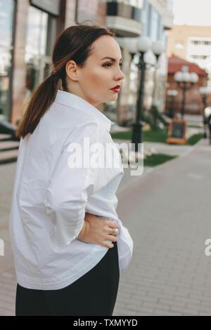 Seria morena mujer elegante dama de negocios en camisa blanca en la calle de la ciudad Foto de stock