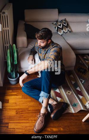 Mitad hombre adulto sentado en el suelo del cuarto de estar mirando a través de la ventana