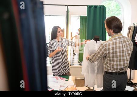 Guapo talentoso diseñador de moda obtener mediciones de un vestido