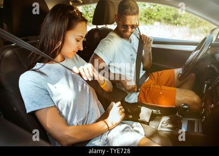 Pareja joven preparándose para sus vacaciones en el coche en día soleado. Mujer y hombre sentado y listo para ir a la mar, el río o el océano. Concepto de relación, vacaciones, Verano, vacaciones, fines de semana.