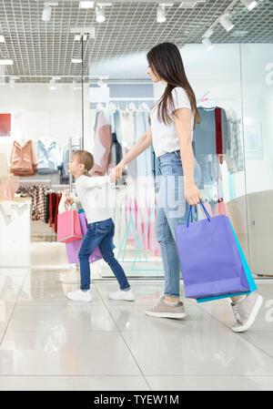 Vista lateral de la joven madre atractiva junto con la pequeña hija de compras en el centro comercial. Chica positivo mantener mano de mujer y funcionando en tiendas. Familia elegir y comprar ropa nueva y juguetes.