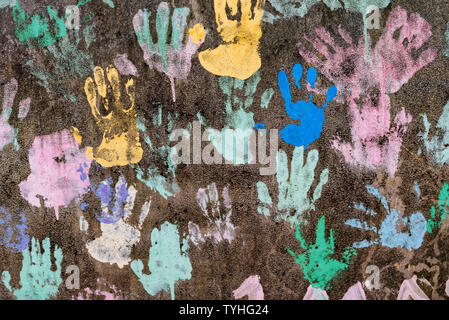 Fondo oscuro con coloridos huella simbolizando amistad interracial Foto de stock