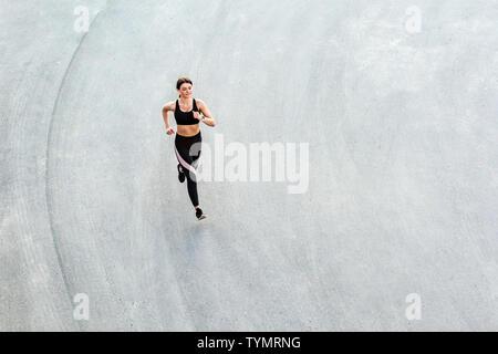 Vista superior del joven atractiva mujer atlética en la ciudad de velocidad el asfalto y entrenar en el tiempo de la mañana en un día soleado de verano. Corredoras capacitación Foto de stock