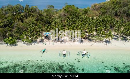Botes filipinos tradicional situado en una playa tropical con palmeras y arenas blancas en un día soleado. Destino de viaje en Filipinas