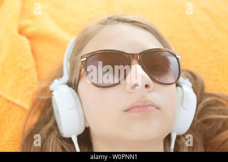 Fascinante joven disfrutando de música favorita en big white auriculares. Cerca foto de niña interior relajado escuchando la canción sobre amarillo backgr aislado Foto de stock