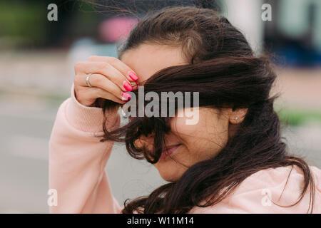 Chica cubre su cara con el cabello y travesuras