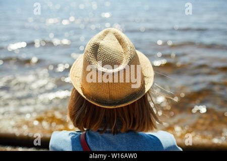 Vista posterior retrato de joven mujer vistiendo sombrero de paja mirando al mar en verano, espacio de copia