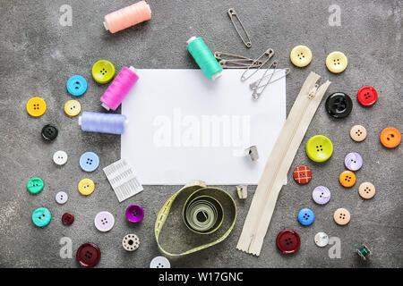 Conjunto de hilos de costura con los accesorios y la hoja de papel sobre fondo gris