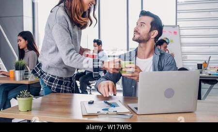 Diseñador de mujer comprar taza de café a un colega en la oficina moderna en la mañana en la recepción.informal estilo de vida en el lugar de trabajo.