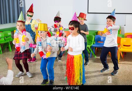 Un grupo de niños de escuela alegre portando sombreros fiesta divirtiéndose con su maestro durante la celebración de la fiesta en la escuela Foto de stock