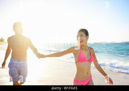 Jóvenes de raza mixta feliz pareja tomados de la mano disfrutando de vacaciones luna de miel en playa soleado de verano. Hermosa raza mixta mujer caucásica de Asia. Hawai Tropical.