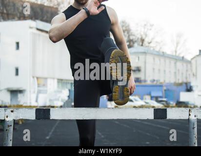 Un hombre en ropa negra es el ejercicio al aire libre con una barrera. fitness atleta en el campo de deportes. La formación con obstáculo. calentar piernas estiramiento del cuerpo.