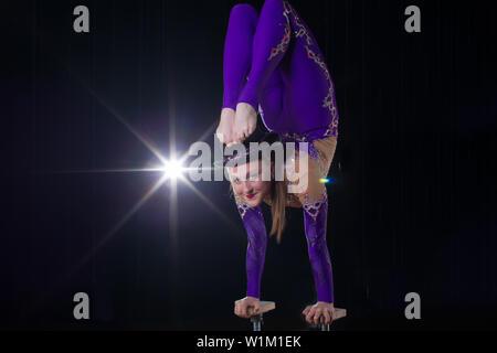 Actriz de circo realiza el número en un bonito humo. Manual del equilibrio de cañas. Chica flexible cuerpo.El rendimiento de un gimnasta de aire en un circo Foto de stock