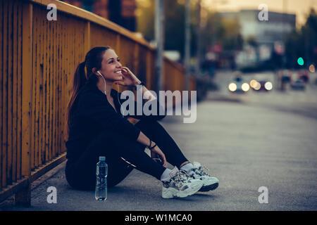 Mujer joven en negro prenda deportiva escuchando música y descansando después de ejecutarse en el puente de la ciudad, en la noche
