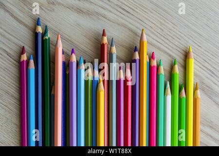 El grupo de una longitud diferente color lápices de dibujo están poniendo sobre la mesa de madera y de fondo a la espera de una lección de pintura.