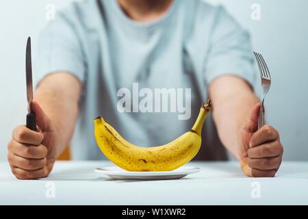 Hombre sentado detrás de una mesa con un tenedor y un cuchillo en la mano y un plátano fresco sobre una placa en una tabla blanca , la hora de comer - Alimentación saludable concepto